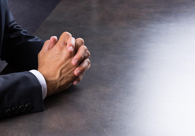 写真:机の上で手を組んでいるスーツの男性