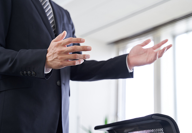 写真:身振り手振りで伝えているスーツの男性